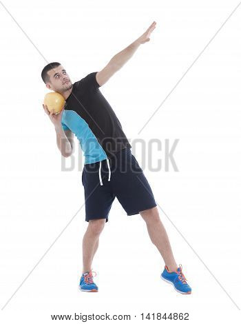 Fit man holding a pomelo in one hand while posing
