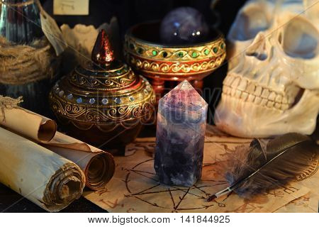 Halloween still life with magic crystal stone, parchment scrolls and skull