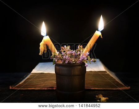 Two candles with herbs against the background of open book in the darkness. Mystic background