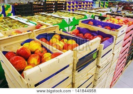 Plenty of apples in the food store in crates. Fruit supermarket.