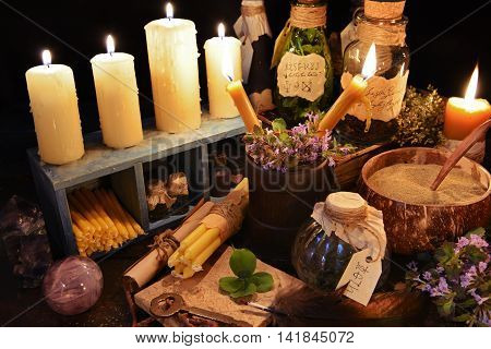 Witch table with burning candles, magic objects and healing herbs. Halloween or alternative medicine image. Signs on bottles labels are not foreign text, these letters are imaginary symbols.