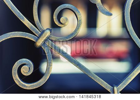 Fragment of figured forged metal fence on a background of colored spots