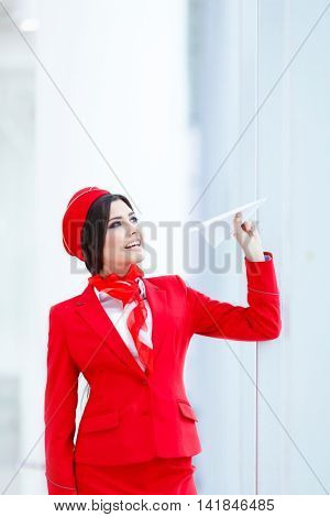 Happy stewardess with a paper airplane