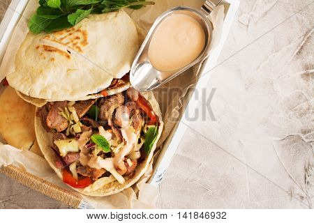 Greek pita bread with meat and salad on wooden tray. Space for text. Selective focus