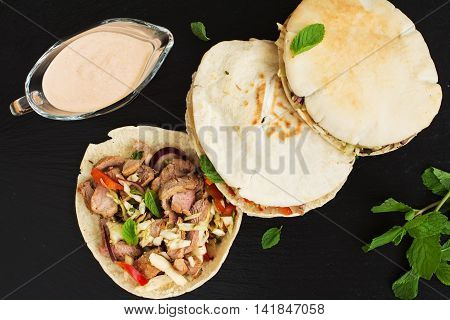 Pita bread with meat and vegetable salad filling served with yogurt sauce and mint leaves. Top view. Selective focus