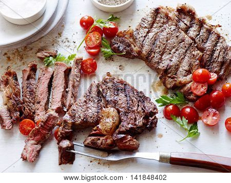 Sliced deep fried beef with tomatoes and herbs on the table