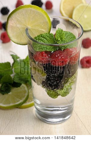 A glass of lemonade from the berries of blackberry and raspberry with lime and mint