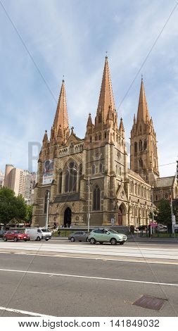Melbourne - February 23 2016: View of the Cathedral of St. Paul the view from Federation Square and the cars driving on the street February 23 2016 Melbourne Australia