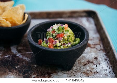 Mixed salad of mashed advocado tomatoes onion and herbs on black bowl
