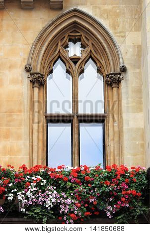 A gothic window with decorations and flowers