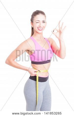 Sporty Girl Holding Centimeter Winking And Smiling
