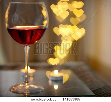 Glass of red wine on blurred romantic background