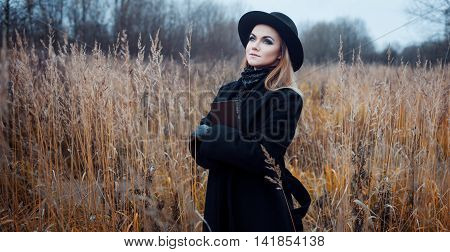 Portrait of young attractive woman in a black coat and hat. She's one in a field reading a book, autumn landscape, dry grass