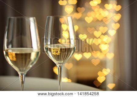 Glasses of wine on romantic blurred background