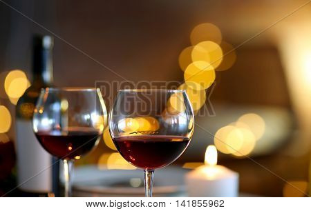 Romantic composition with wine and candle on blurred background
