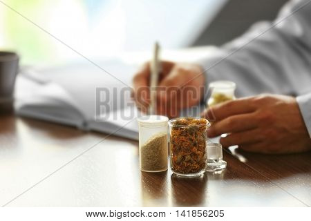 Bottles with dry inflorescence and doctor on background. Herbal medicine concept