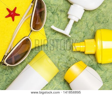 Various cosmetic sunscreen products for face and body skin care towel and sunglasses. Lotion, milk, spray and cream. Cosmetics containing sun protection factor