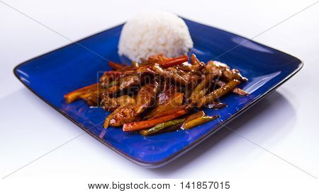 Chicken teriyaki on blue chinese plate on white background
