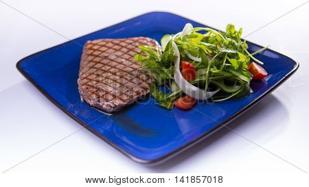 Tuna steak with meat dressing shouts on blue chinese plate on white background