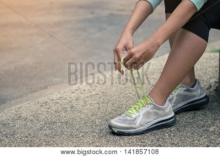 Running shoes - closeup of woman tying shoe laces. Female sport fitness runner getting ready for jogging outdoors on forest path in spring or summer with vintage and close up photo.