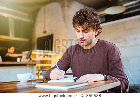 Concentrated thoughtful handsome attractive curly guy in brown sweetshirt planning his schedule sitting in cafe
