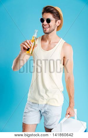 Cheerful young man in hat and sunglasses holding cooler bag and drinking beer over blue background