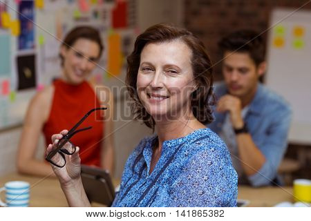 Portrait of smiling businesswoman holding spectacles in office