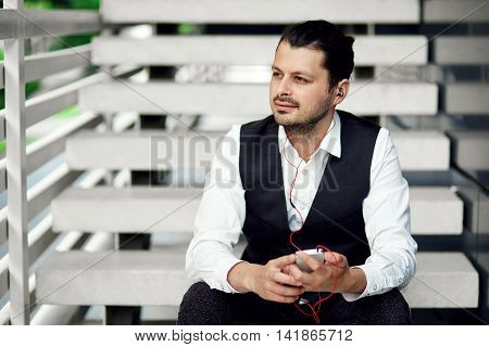Handsome male relaxing on steps and listening music. Portret of a attractive man outdoors with a smartphone in hands