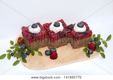raspberry cake slices on a wooden board - banana chocolate wholemeal tart and raspberries in glaze filling. Decorated with fresh blueberries. Selective focus.