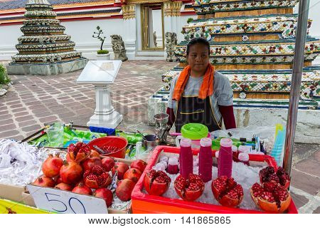 Wat Pho area. Bangkok Thailand - Jun 27 2016. Thai woman selling fresh handmade pomegranate juice inside Wat Pho area. Bangkok Thailand
