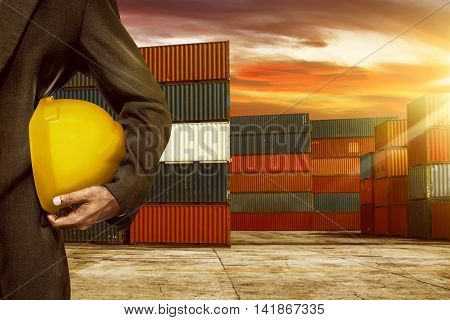 Woman hand holding yellow helmet in the port with container background