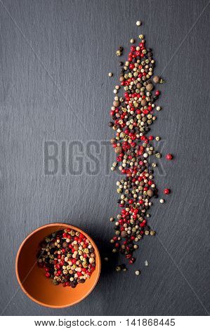 pepper in pottery and spilled pepper on a slate board. top view