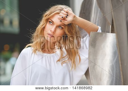 Beautiful pensive woman in white blouse leaning on steel sculpture with hand touching her forehead