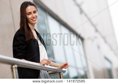 Happy young girl with long brunette hair leans on railing against building and smiling