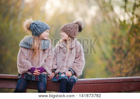 Two adorable girls in forest at warm sunny autumn day