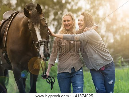 two woman walking with horse at a farm