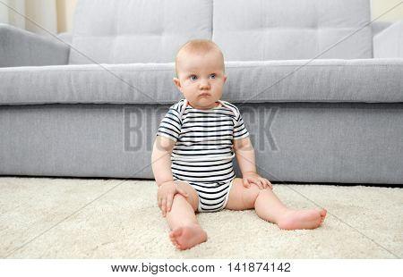 Adorable little baby sitting on light carpet
