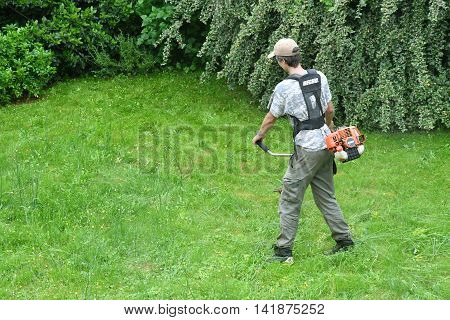Verneuil sur Seine France - june 27 2016 :a woman is cutting lawn in a garden with a String trimmer