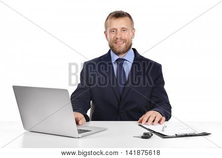 Seller man at table with laptop and car key isolated on white