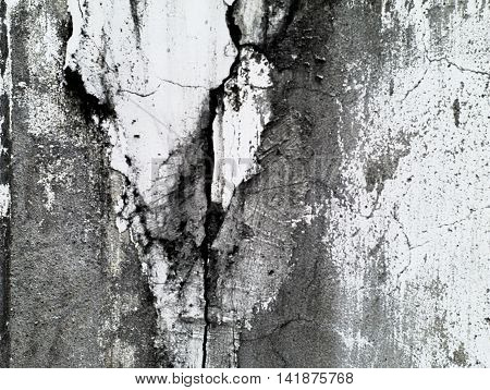 old and decayed white cement wall with cracks and stains