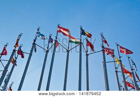 different flags on background of the blue sky