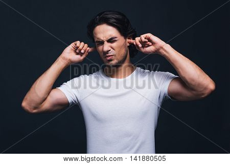 This is too loud. Handsome young man expressing negativity and covering ears by hands while standing against grey background