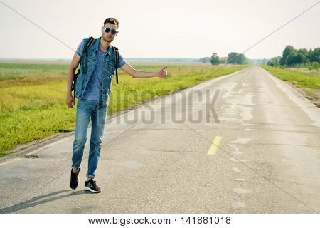 Handsome young man hitchhiker standing on a highway. Adventure and tourism concept. Jeans style.
