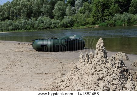 A sand castle and a rubber boat on the river.