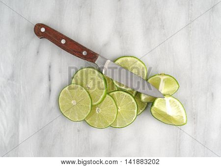 Several slices of limes plus a knife on a gray marble cutting board.