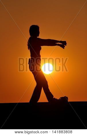 Bang Saen Thailand - January 10 2014: A tai 'chi instructor standing on a platform silhouetted by the setting sun giving a class at a seaside park