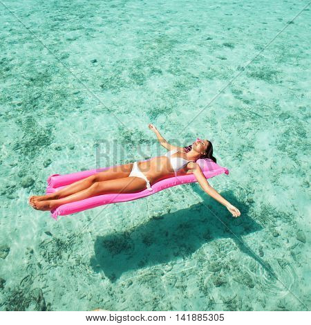 Woman relaxing on inflatable mattress in the sea