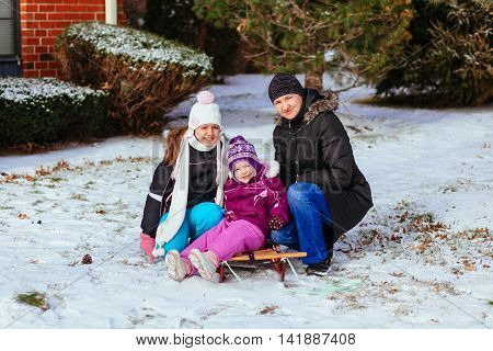 Young mother and her daughters having fun on winter day little girl playing in the street in winter