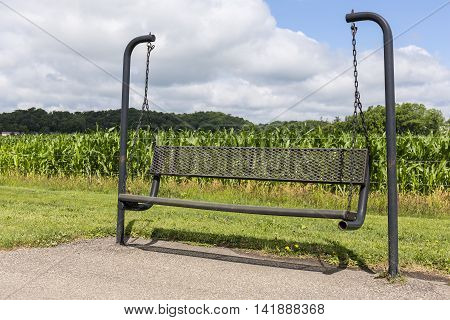 A black park bench swing with a cornfield in the background.