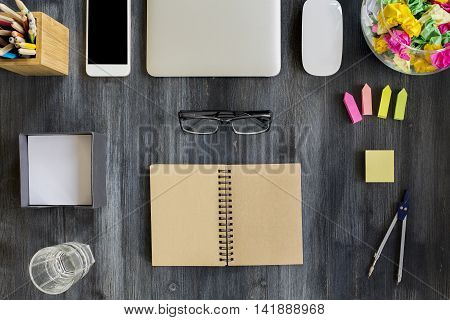 Top view of dark wooden desktop with open spiral notepad blank smartphone closed laptop glass of water and supplies. Mock up